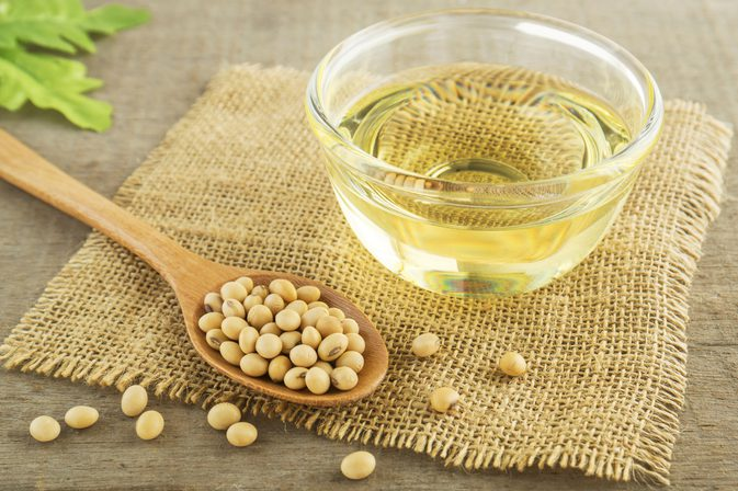 soybean oil in cup on burlap next to raw beans in wooden spoon
